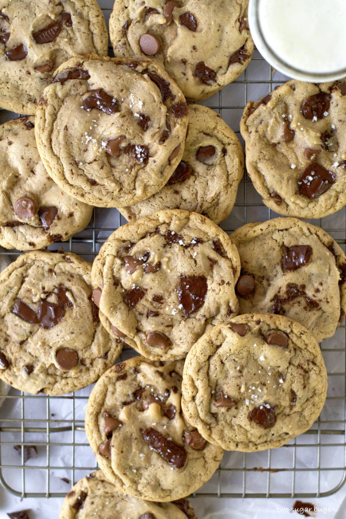 pile of chocolate chip cookies on a wire cooling rack with a glass of milk
