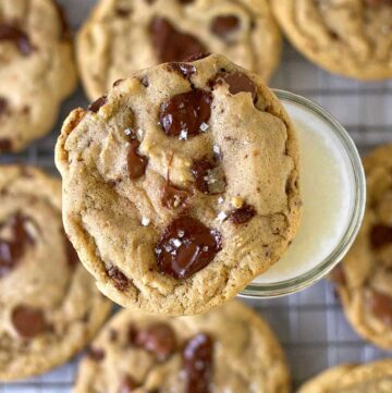 malted chocolate chip cookie sitting on top of a glass of milk