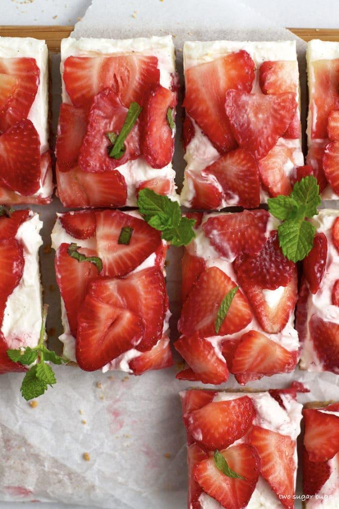 overhead look at no bake mascarpone cheesecake bars with fresh strawberries and mint