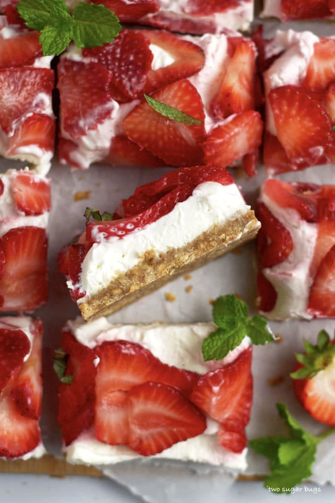 bar on it's side to show the graham cracker layer, mascarpone layer and fresh strawberries