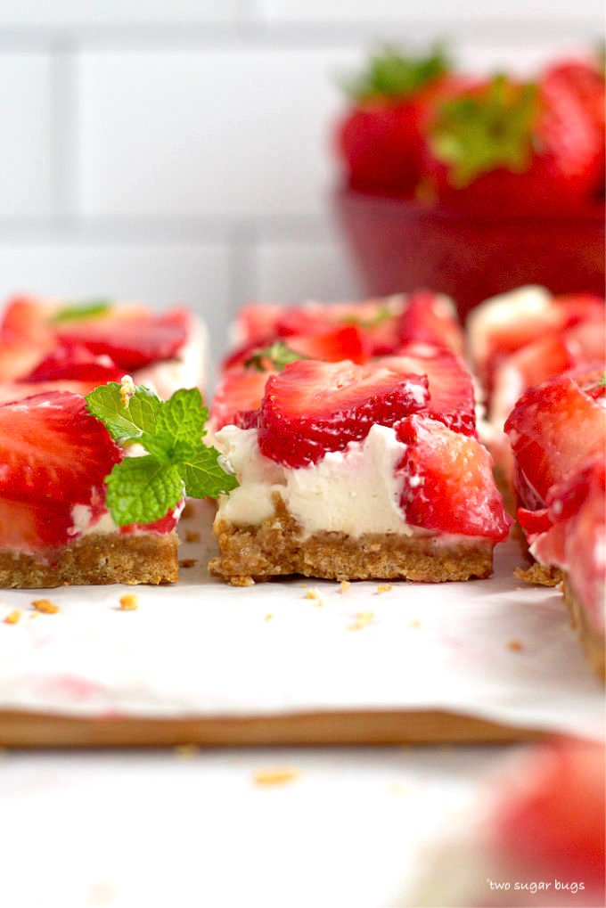 no bake mascarpone cheesecake bars on a parchment lined cutting board