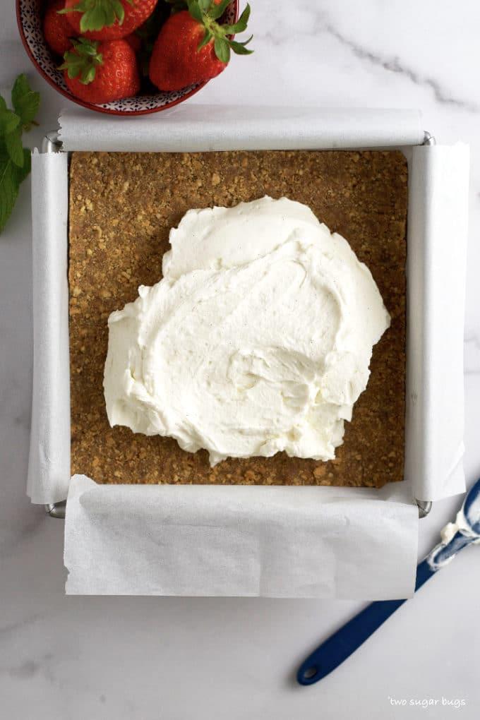 mascarpone layer being added to vanilla graham cracker crust