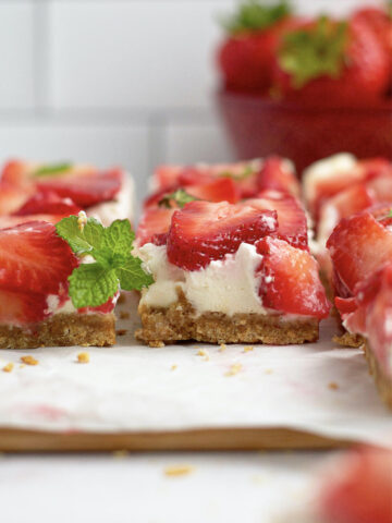 side view of mascarpone cheesecake bars with mint and strawberries