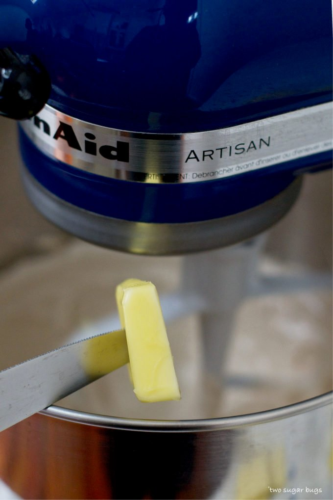 butter being added to the mixer with a knife