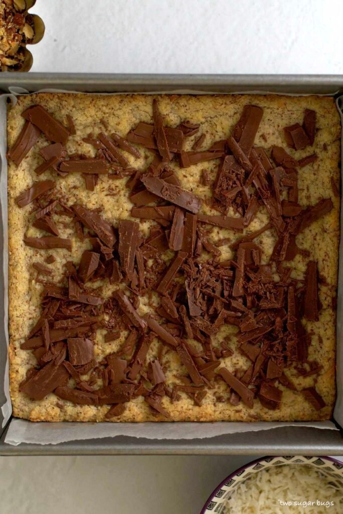 chopped chocolate melting over almond flour cookie base