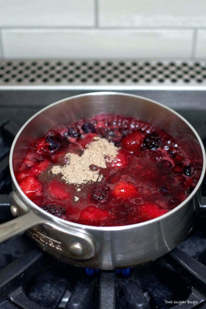 cardamom on top of berries in a saucepan