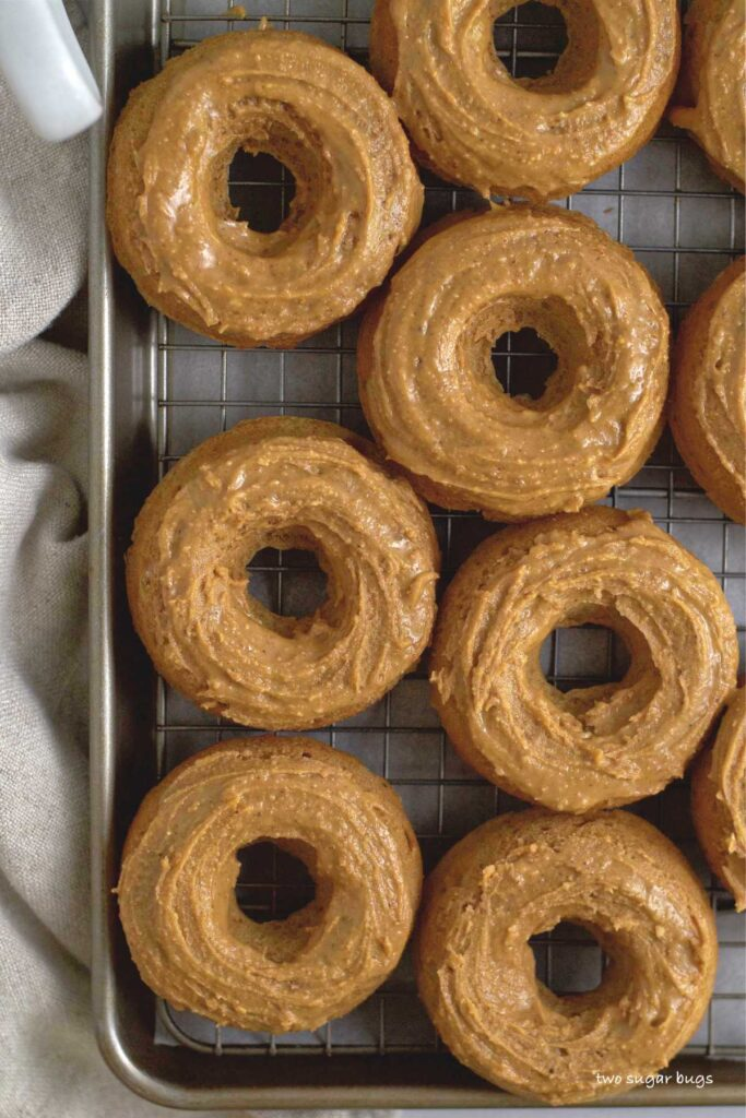 baked and glazed donuts on a baking pan