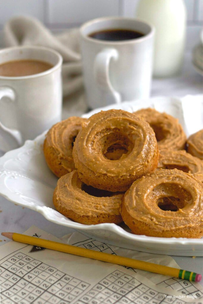 peanut butter donuts on a serving tray with cups of coffee