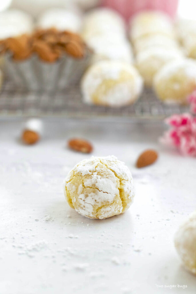 amaretti cookie sitting on confectioners' sugar covered counter