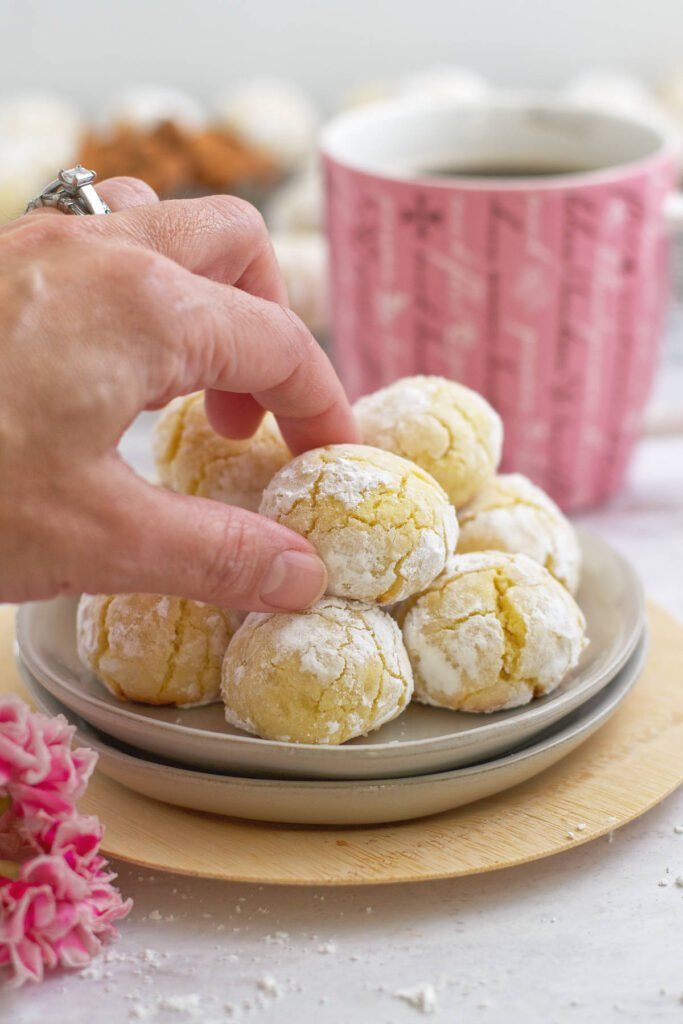 hand reaching for a soft amaretti cookie on a plate