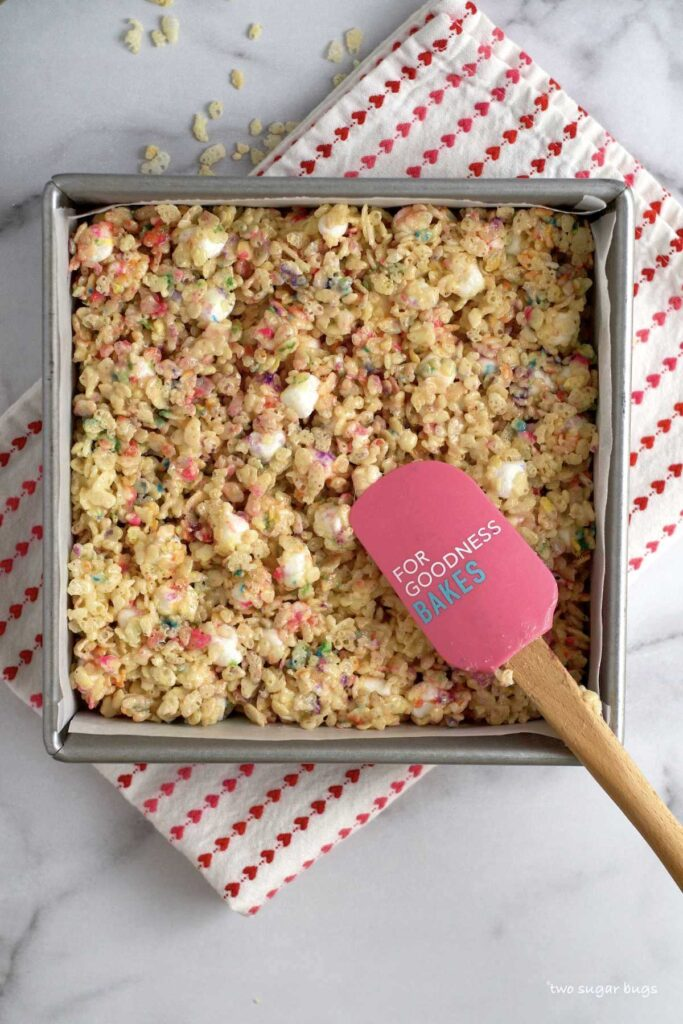 spatula lightly pressing finished cereal bars into baking pan