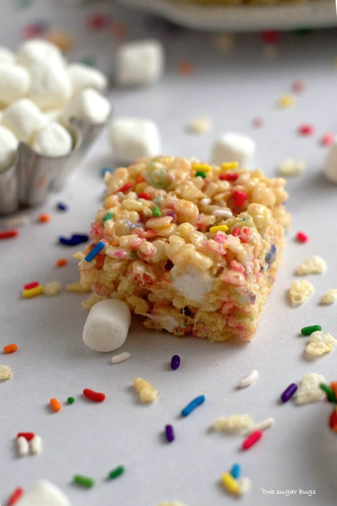 single krispie bar with a bowl of marshmallows in the background