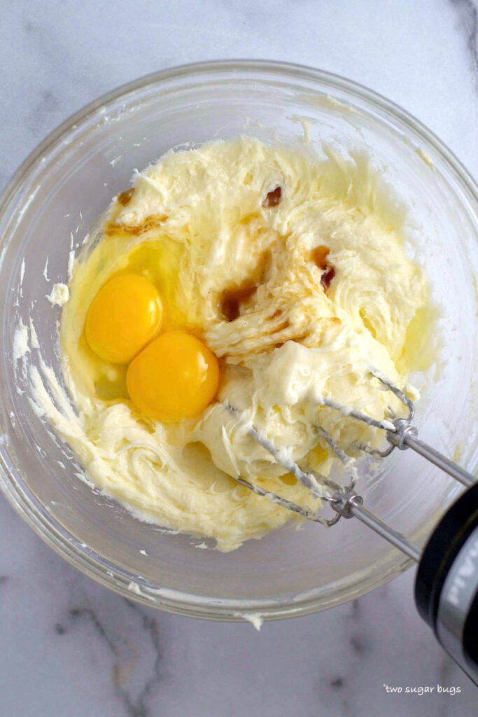 eggs, vanilla and almond extract being added to sugar cookie ingredients